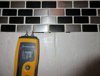 Moisture meter indicates elevated readings to bathtub / shower tile enclosure