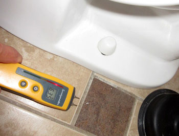 Moisture meter indicates elevated readings to floor by toilet